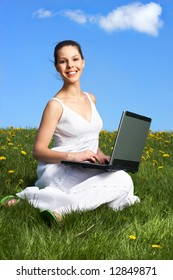 Beautiful young woman working with laptop under blue sky.