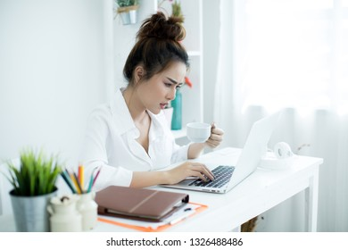 Beautiful young woman working on her laptop in her room.