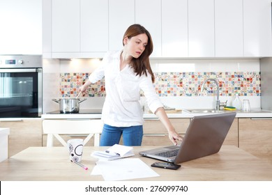 Beautiful young woman working on laptop and cooking at the same time