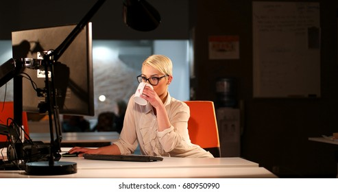 beautiful young woman working on computer at night in dark office. The designer works in the later time.