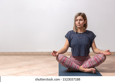 Beautiful young woman working out in loft interior on white background with copy space, doing yoga exercise on mat, Sitting in Siddhasana, Half Lotus Posture, meditating, breathing, close-up