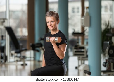 Beautiful Young Woman Working Out Biceps In A Health Club