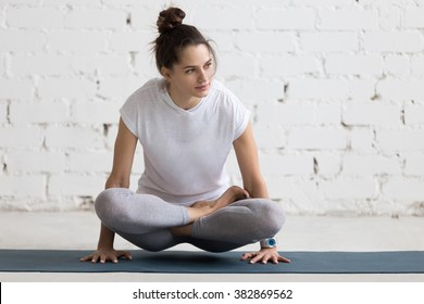 Beautiful young woman working out in loft interior, doing yoga exercise on blue mat, arm balance exercise with crossed legs, Scale Posture, Tolasana, Utpluthi Pose, full length