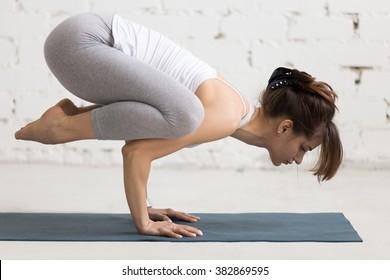 Beautiful young woman working out indoors, doing yoga exercise on blue mat, handstand asana, exercise for shoulders strength, Crow (Crane) Pose, Kakasana (Bakasana) with arms bent, full length