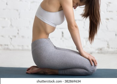 Beautiful young woman working out in loft interior, doing yoga exercise on blue mat, holding the breath while performing Upward Abdominal Lock, Uddiyana Bandha, close-up