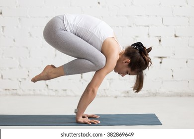 Beautiful young woman working out indoors, doing yoga exercise on blue mat, handstand asana, exercise for arms and wrists strength, Crane (Crow) Pose, Bakasana with arms straight, full length