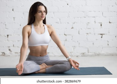 Beautiful young woman working out in loft interior, doing yoga exercise on blue mat, Sitting in Easy (Decent, Pleasant Posture), Sukhasana, asana for meditation, pranayama, full length, copy space