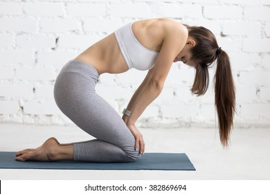 Beautiful young woman working out in loft interior, doing yoga exercise on blue mat, performing Upward Abdominal Lock, Uddiyana Bandha, full length