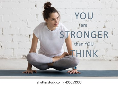 "Beautiful young woman working out in loft interior, doing yoga exercise on blue mat. Motivational phrase ""You are stronger than you think"""