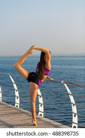 Beautiful young woman working out at the seaside