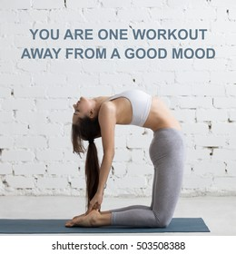 "Beautiful young woman working out in loft interior, doing yoga exercise, stretching, standing in Ustrasana, Camel Posture, full length. Motivational text ""You are one workout away from a good mood"""