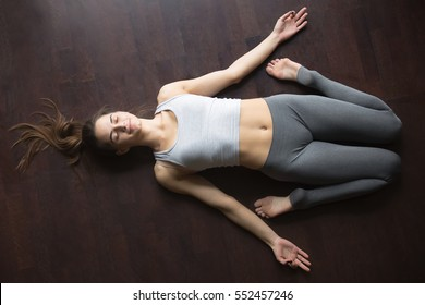 Beautiful young woman working out at home, doing yoga exercise on wooden floor, lying in Reclining Hero pose, Supta Virasana posture, resting after practice. Full length, top view