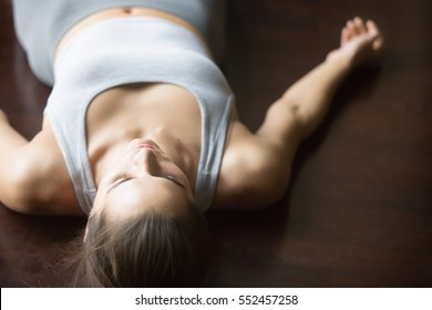 Beautiful young woman working out at home, doing yoga exercise on wooden floor, lying in Shavasana (Corpse or Dead Body Posture), resting after practice, meditating, breathing. Close up