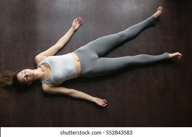 Beautiful young woman working out at home, doing yoga exercise on wooden floor, lying in Shavasana (Corpse or Dead Body Posture), resting after practice, meditating, breathing. Full length, top view