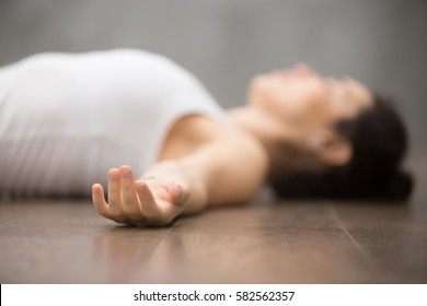 Beautiful young woman working out on wooden floor, resting after doing yoga exercises, lying in Shavasana (Corpse or Dead Body Posture), relaxing. Close up, focus on hand