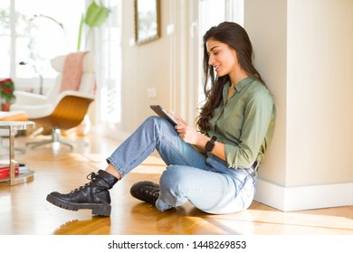 Beautiful young woman working using touchpad tablet sitting on the floor