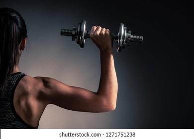 Beautiful young woman workout with dumbbell over gray background