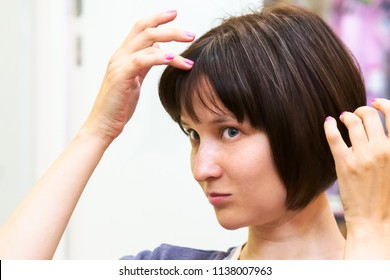 Beautiful young woman is worried about her first grey hair.