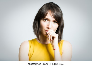 beautiful young woman worries and bites her nails, isolated on background
