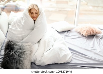 Beautiful young woman wrapped in soft blanket sitting near window at home. Winter atmosphere