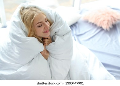 Beautiful young woman wrapped in soft blanket at home. Winter atmosphere