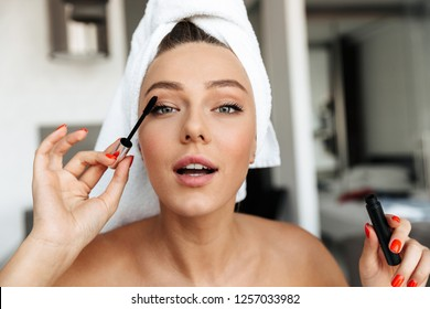 Beautiful young woman wrapped in a towel doing her eye makeup