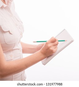 A beautiful young woman writes on the document table