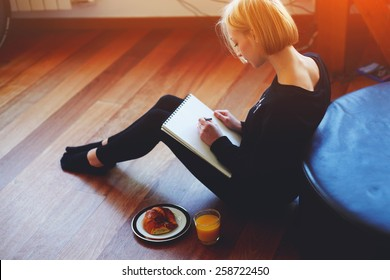 Beautiful young woman writing something in the note pad while sitting on the floor at living room, charming female studying doing homework at home, girl writes diary at her breakfast, flare light