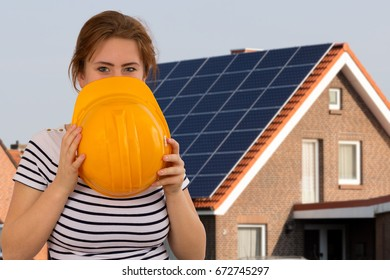 beautiful young woman with yellow helmet in front of house with solar panels