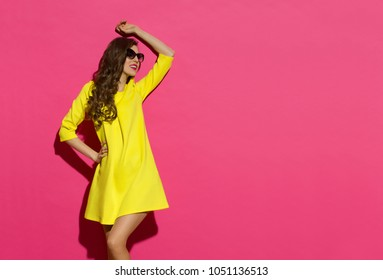 Beautiful young woman in yellow mini dress and sunglasses is posing with arm raised and looking away. Three quarter length studio shot on pink background.