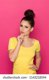 Beautiful young woman in yellow top is holding hand on chin, looking at camera and grimacing. Waist up studio shot on pink background.
