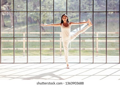 Beautiful young woman yoga instructor doing vrikshasana standing on one leg against the background of a spacious window overlooking the beautiful nature. Concept of flexibility and joint health