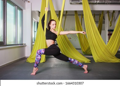 Beautiful young woman, yoga instructor practicing fly yoga in the gym.