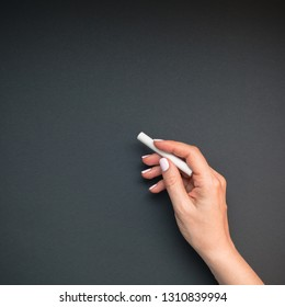 Beautiful young woman's hand with pastel pink manicure holding piece of chalk on blackboard background. School concept. Template for feminine blog social media