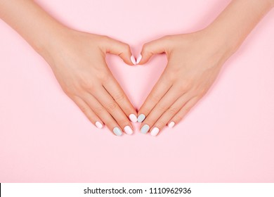 Beautiful young woman's hand with perfect manicure making heart on pink background. Flat lay style.