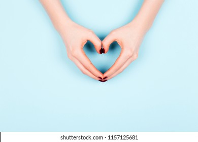 Beautiful young woman's hand with perfect manicure making heart on blue background. Flat lay style.