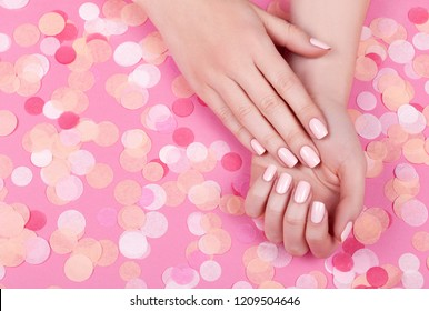 Beautiful young woman's hands on pink pastel background with festive multi color confetti.