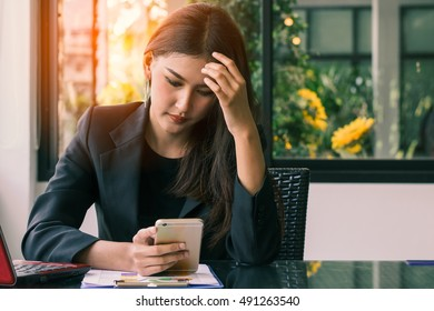 Beautiful young women ,a businesswoman use a laptop and smart phone to work ,working in the office