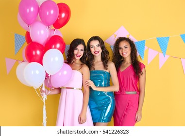 Beautiful young women with air balloons on yellow background