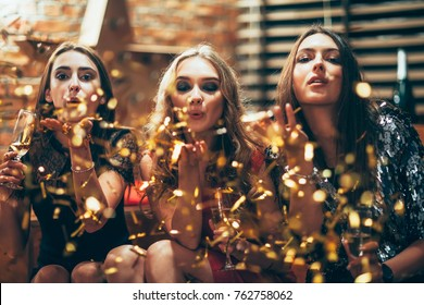 Beautiful young women blowing confetti on party. New year, Birthday, Holiday Event, Fun concept