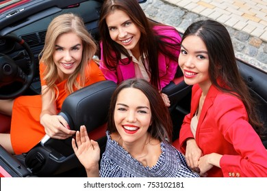 Beautiful young women in cabriolet outdoors