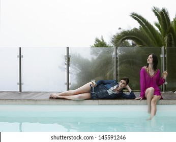 Beautiful young women with champagne glasses by outdoor pool