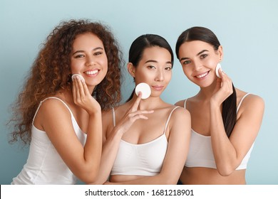 Beautiful young women with cotton pads on color background