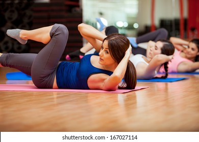 Beautiful young women doing crunches during a class at a gym
