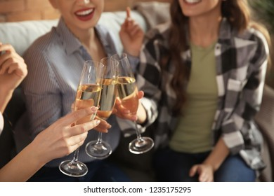 Beautiful young women drinking champagne at home