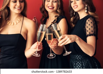 Beautiful young women drinking champagne on color background