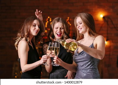 Beautiful young women drinking champagne at party