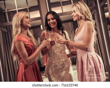 Beautiful young women are drinking champagne and smiling while choosing elegant wedding dress in modern wedding salon