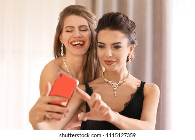 Beautiful young women with elegant jewelry taking selfie indoors