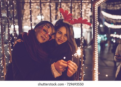 Beautiful young women enjoying Christmas or New Year night on a city street.